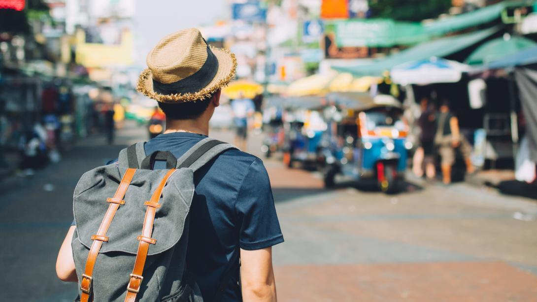 Viajero explorando un mercado para aprender hábitos de consumo responsable.